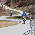 Bicyclists zoom down the South Dry Sac Greenway Trail just before it crosses beneath Missouri 13 near Springfield. Ozark Greenways maintains more than 75 miles of urban and rural trails in Greene County, including a 6-mile water trail on the James River, with plans to build more trails.