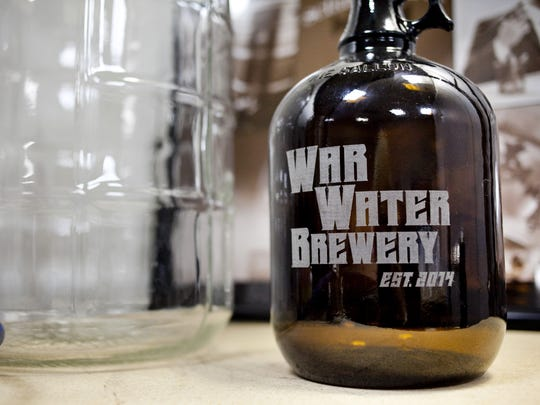 A War Water Brewery growler marks the new brewery Kris Paul opened inside a storefront within the Riverview Plaza. A growler sits on a table Thursday, March 26, 2015 at War Water Brewery in St. Clair. The temporary location has been set up at 201 N. Riverside Ave., Suite C-12, until a location for a larger commercial brewing operation is established.