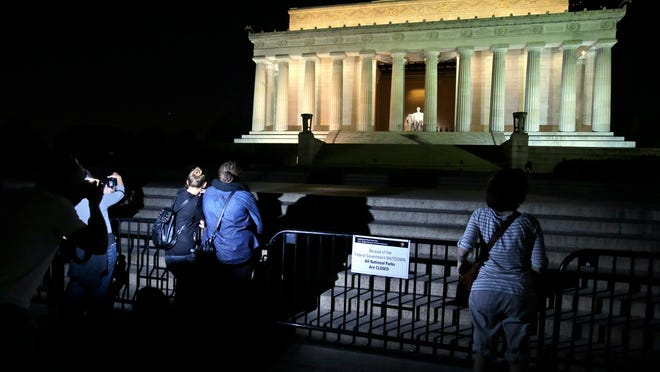 People take pictures in front of the steps of the closed Lincoln Memorial, Tuesday, Oct. 1, 2013, in Washington. The museums that draw millions of visitors to the National Mall closed their doors Tuesday, memorials were barricaded and trash will go uncollected in the nation's most-visited national park due to the first government shutdown in 17 years.  (AP Photo/Alex Brandon) ORG XMIT: DCAB105