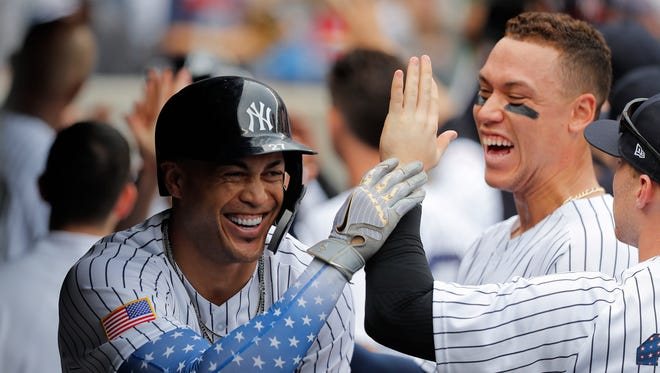 New York Yankees' Giancarlo Stanton, left, celebrates with teammates, including Aaron Judge, rear right, after hitting a three-run home run against the Atlanta Braves during the third inning of a baseball game, Wednesday, July 4, 2018, in New York.