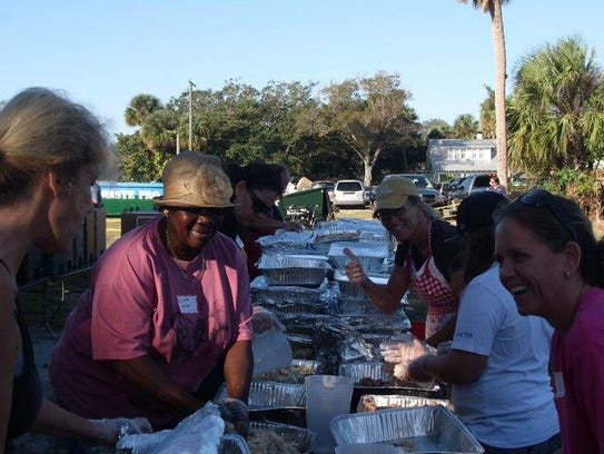 Linda Norman (center in the hat) carves turkeys before