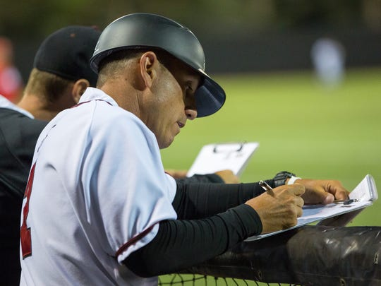 NMSU head baseball coach Brian Green look over his clipboard on Tuesday during the NMSU/ UNM game.