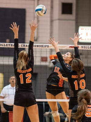 Northville's Jenna Boksha (middle) drills one over the net against Rockford's Emmy Webb (12) and Megan Witte (10) during MHSAA volleyball semifinals against Rockford at the Kellogg Arena in Battle Creek.