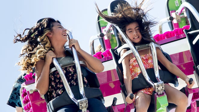 Desyre Munoz (10, right) and her sister, Destiny Munoz (15) ride the Tango, October 10, 2014, at the Arizona State Fair.