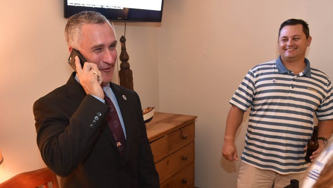 """Albert Iovino, of Sebastian (left), takes a congratulatory phone call from current Sebastian Mayor Bob McPartlan, after winning a seat on the Sebastian City Council on Nov. 7, 2017, at Portside Pub & Grill as supporter Jesse Hall stands on right. """"I'm excited to work with the other council members and the work for the city,"""" Iovino said."""