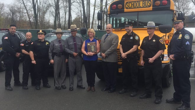 Wendy Travis, a bus driver for the Wappingers Central School District, was given the 16th annual School Bus Driver of the Year Award. She stands with Dutchess County Traffic Safety Board Administrator William Johnson and members of local law enforcement.