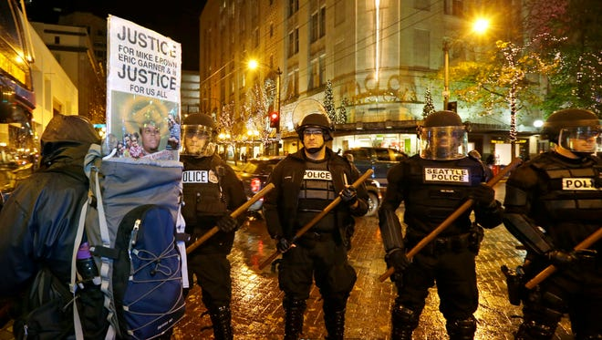 """Police with wooden sticks stand guard next to a protester with a sign that reads """"Justice for Mike Brown, Eric Garner, and justice for us all,"""" Monday, Dec. 8, 2014, after they cleared a group of protesters out who had stopped traffic at 4th and Pine in downtown Seattle"""