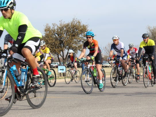 Bicyclists race from the starting line Saturday for