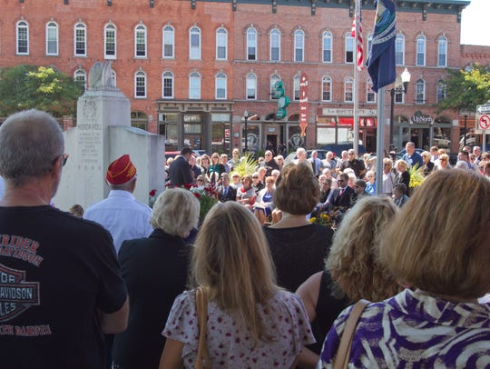 A large crowd surrounds Howell's Veterans Memorial