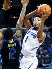 Memphis guard Jamal Johnson (right) drives to the basket by Tulsa defender DaQuan Jeffries (left) during second half action at the FedExForum in Memphis Tenn., Saturday, January 6, 2017.