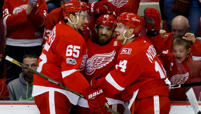 Red Wings left wing Henrik Zetterberg (40) receives congratulations from defenseman Danny DeKeyser (65) and right wing Gustav Nyquist (14) after scoring in the second period of the Wings' 2-1 overtime loss Friday at Joe Louis Arena.
