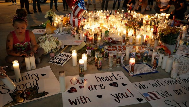 A girl places candles at a memorial for victims of the mass shooting Tuesday, Oct. 3, 2017, in Las Vegas. AP