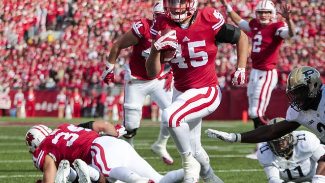 Wisconsin linebacker Nick Thomas (45) runs for a touchdown against Purdue defensive end Antoine Miles (11) and cornerback Stefan Certa (26) during the first half of an NCAA college football game Saturday, in Madison.