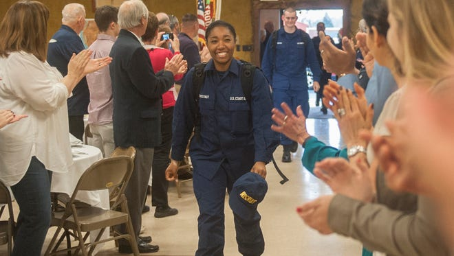 U.S. Coast Guard cadet Taylore Chestnut (cq) of Chesapeake, VA., center, receives a standing ovation from volunteers as Chestnut  and other U.S. Coast Guard cadets stationed in Cape May arrived to a Christmas party held by the Millville Elks Lodge 580 for cadets on Friday.  12.25.15