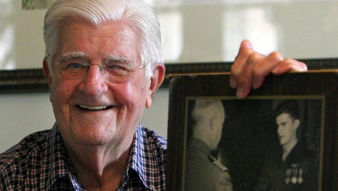Jerry O'Keefe of Biloxi holds a photograph in June 2007 of him receiving medals for his exploits as a Marine pilot during World War II.