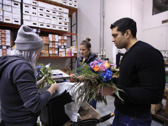 Ajay Kori, right, owner of UrbanStems, in Washington, helps Megan Sanders, left, and Mary Beth Gearino, center, prepare fresh flowers for delivery at the company's warehouse in Washington.