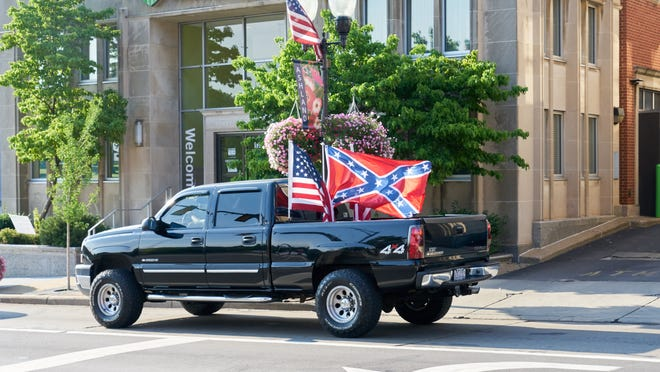 A truck flies a Confederate flag next to an American flag and a Thin Blue Line flag as it passes by Black Lives Matter protesters at Main Street and Claremont Avenue Thursday evening. Protesters have occupied that corner every day for over a month.