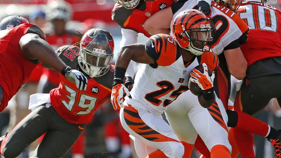 Cincinnati Bengals running back Giovani Bernard (25) hits a hole during the second quarter of their game against the Tampa Bay Buccaneers played at Raymond James Stadium in Tampa, Florida Sunday November  30, 2014. The Enquirer/Gary Landers