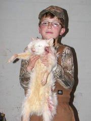 Taylor Lindsey with an albino raccoon he treed on a