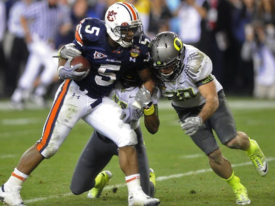 Auburn running back Michael Dyer (5) is stopped by Oregon safeties Eddie Pleasant (11) and John Boyett (20) in the BCS National Championship Game on Monday January 10, 2011, at the University of Phoenix Stadium in Glendale, AZ.
