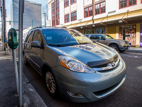 An minivan used by an Uber X driver parked in downtown