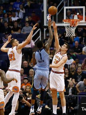 Memphis Grizzlies forward Jarell Martin (1) gets off a shot over Phoenix Suns forward Dragan Bender (35) and center Alex Len (21) during the first half of an NBA basketball game, Tuesday, Dec. 26, 2017, in Phoenix.