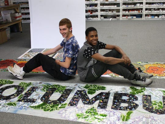 Eli Gaccione, 17, of Johnson City, and Jacky Henry, 15, of Binghamton, with a mosaic they helped create for Columbus Park.