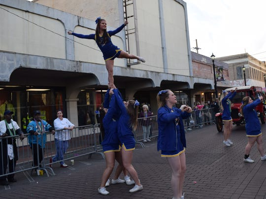 The Southern Arkansas University cheerleaders perform in the Hixson Classic Cars & College Cheerleaders Parade on Friday in downtown Alexandria.