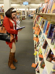 Tony Lockwood looks at books with her daughter, Annabel Lockwood, at 2nd & Charles bookstore in Bossier City.