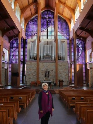 Elizabeth Devereaux stands in front of the completed window.
