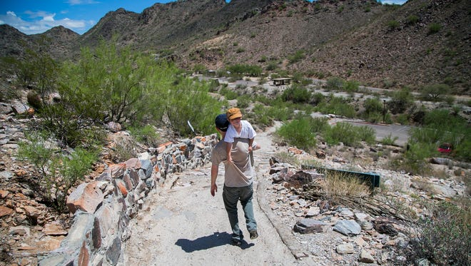After a hike up Piestewa Peak in August, Daniel Steinmetz gets a ride down the trail from his father, Yosef.