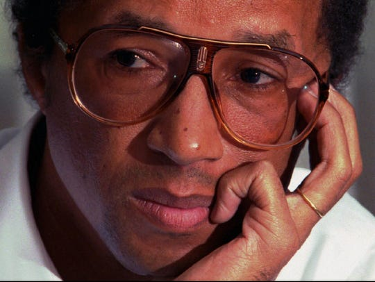 Tennis great Arthur Ashe listens to a reporter's questions
