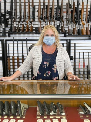 Dawn Dennis, manager of the Alliance Loan Co. in Alliance, stands at the gun counter. The pawn shop found the guns to be popular purchase and pawn as peoples' financial health came and went with the federal stimulus checks and unemployment payments.