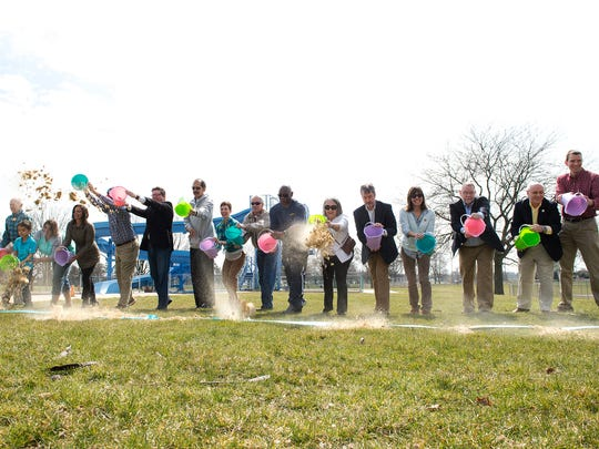 Officials with the Borough of Chambersburg and other community members throw sand on the blue ceremonial ribbon for the groundbreaking for its new Aquatic Center on Saturday, March 25, 2017 in Chambersburg, Pa. The same blue ribbon will be used for the ribbon cutting ceremony once the center is ready.