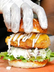 In this March 1, 2017, photo, a handler tops a Krispy Fried Chk'n sandwich with a doughy pretzel bun in Miami. The fare is popular among vegans and vegetarians who long for greasy comfort food, but abstain for ethical reasons.