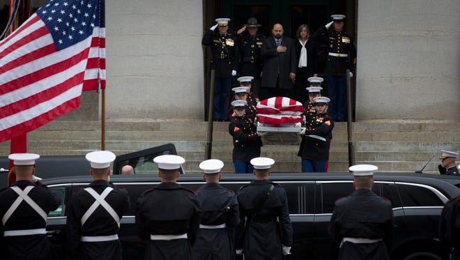 U.S. Marines transport the body of Sen. John Glenn outside of the Ohio Statehouse, where he lay in repose the previous day, to begin his funeral procession.