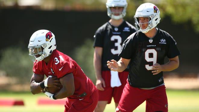Arizona Cardinals quarterback Sam Bradford hands the ball to running back David Johnson during voluntary Organized Team Activities on May 15, 2018 at the Arizona Cardinals Training Facility in Tempe, Ariz.