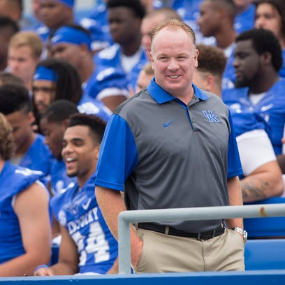 Kentucky's head coach Mark Stoops watches over his team as they have their photo taken during media day.