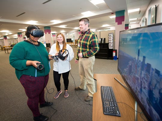 Ebony Preston, a junior elementary education major from Yazoo City, explores New York City using virtual reality equipment in MSU Libraries' new CAVS Mixed Reality Lab as Katelyn Cheatham, a graduate student in English from Philadelphia, and MSU Libraries Instructional Technology Specialist Thomas La Foe look on.