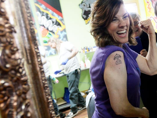 Mary Thoma reacts when she sees her tattoo for the