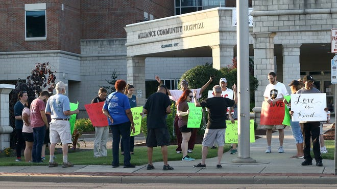 Alliance Friends Church members holding a prayer vigil in front of Aultman Alliance Community Hospital after walking from the church on West State Street and stopping at the University of Mount Union. Church members made four stops along the route.