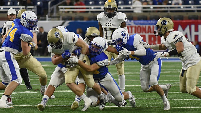 Country Day's Chris Bergin (5), center, tries to rush past Grand Rapids Catholic Central's defense.