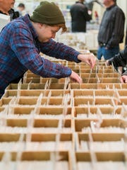 """Ryan Boyle looks for """"golden age"""" comics, comic books from before 1950, at the First State Comic Con at the Mill Creek Fire Hall on Sunday morning."""