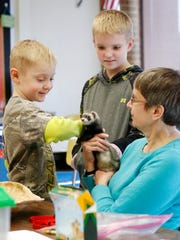 Cousins Nelson Cleveland IV, 6, left, and Shawn Hable, 12, both of the Horseheads area, pet and learn about Ferris the ferret by Gail Norwood from Tanglewood Nature Center & Museum.