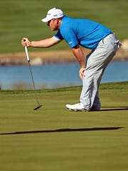 Chad Pfeifer bends down to read the ninth green at