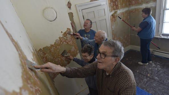 Scrapers in hand, volunteers remove layers of wallpaper