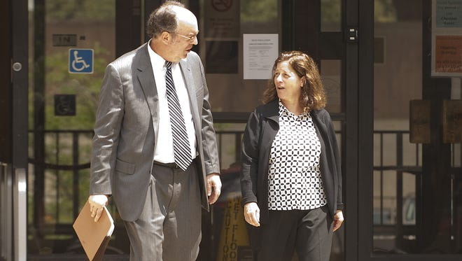 Debra Bulter walks out of the Keating Federal Building with her attorney, William Easton, in 2013
