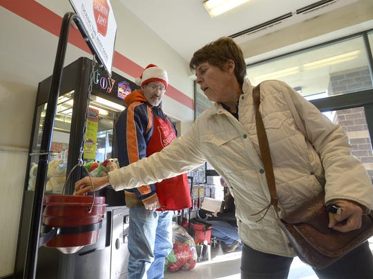 Debbie Briscoe donates to the Salvation Army as bell ringer Jimmy Melton looks on, Tuesday afternoon, on the National Day of Giving.