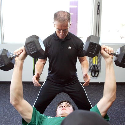 Larry Miller, of Max Life Fitness, works with Cody Dennis, 18, Thursday evening at the South 30th Street location.