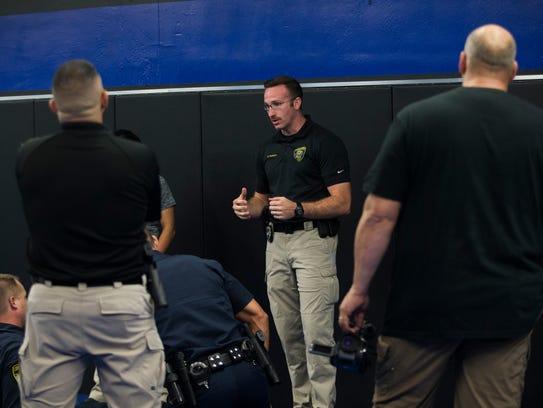 Officer Braden Tackett (center) critiques cadets after